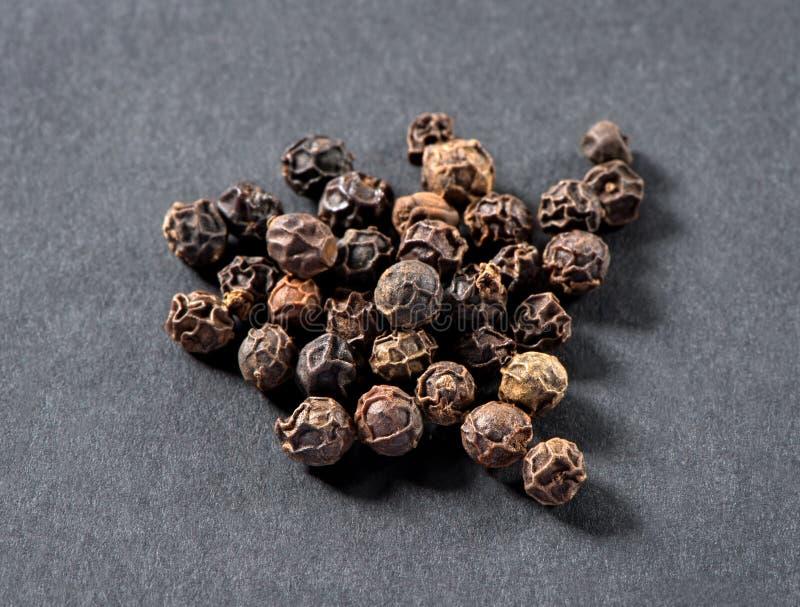 Het close-up van zwarte pepererwten op grijze steenachtergrond stock afbeelding