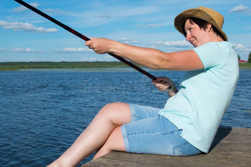 Het close-up, vrolijke vrouw in een hoed op een pijler, houdt een hengel en trekt een vissenvangst, op de achtergrond van mooi te royalty-vrije stock foto