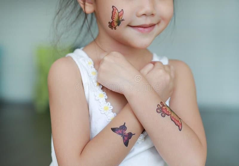 Het close-up weinig kindmeisje met de sticker van de vlindertatoegering op lichaamshuid, kleedt omhoog tatoegeringen stock fotografie
