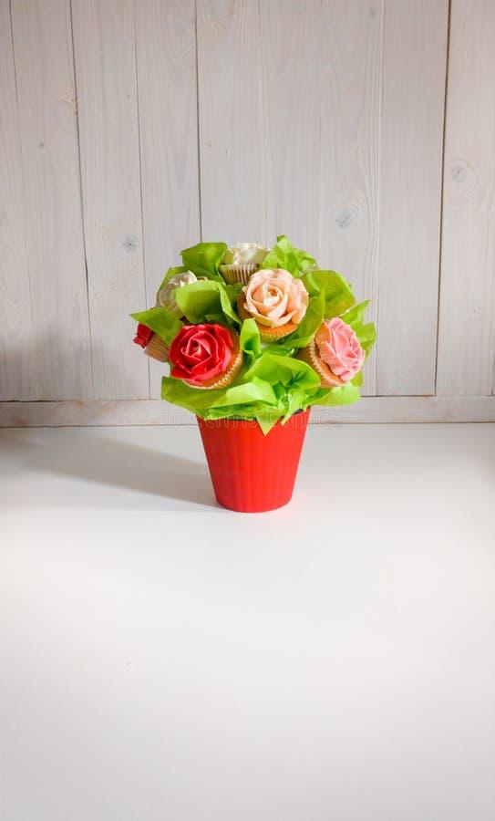 Het close-upbeeld van boeket in rode pot maakte van cupcakes tegen witte houten achtergrond Mooi schot van snoepjes en stock afbeeldingen