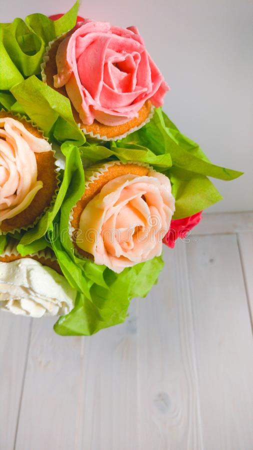 Het close-upbeeld van boeket in rode pot maakte van cupcakes tegen witte houten achtergrond Mooi schot van snoepjes en stock foto's