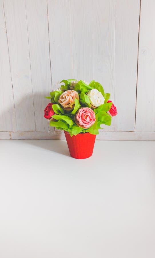 Het close-upbeeld van boeket in rode pot maakte van cupcakes tegen witte houten achtergrond Mooi schot van snoepjes en royalty-vrije stock afbeelding