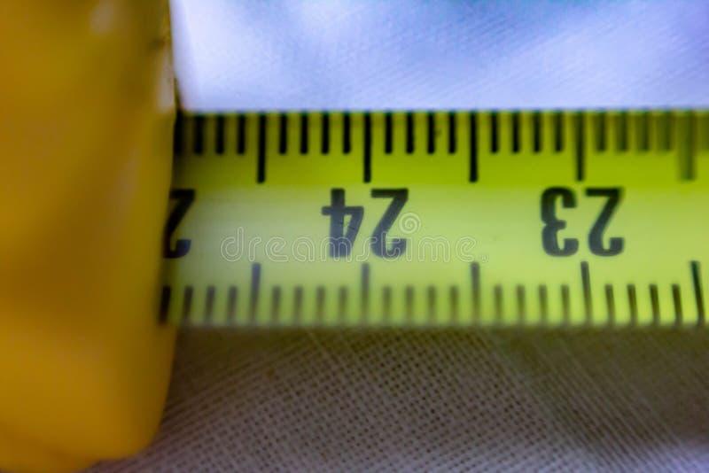 Het close-upbeeld van een geel-gekleurde broodjesmeter in centimeters, u kan de streepjes ook zien die de millimeter merken stock afbeeldingen