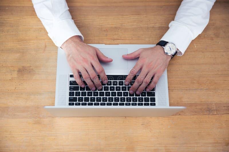 Het close-upbeeld van een zakenman overhandigt het gebruiken van laptop stock fotografie
