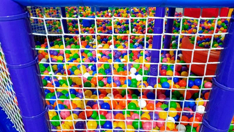 Het close-upbeeld van groot poolhoogtepunt van kleurrijke plastic bal op de kinderenspeelplaats schermde met netto voor jonge gei stock afbeeldingen