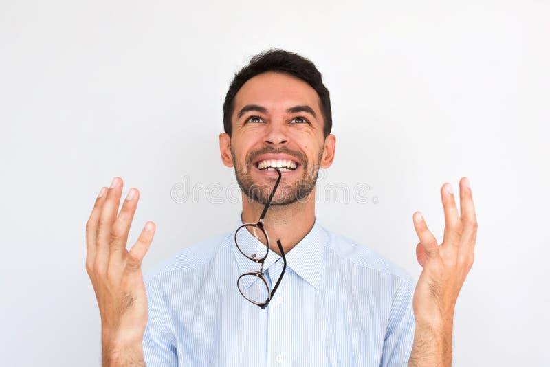 Het close-upbeeld van vrolijk positief jong Kaukasisch mannetje met bril in mondwinsten, gebaren met geluk, draagt blauw overhemd stock afbeelding