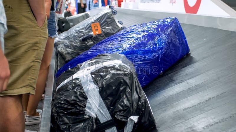 Het close-upbeeld van zakken en de koffers op bagage eisen lijn bij moderne luchthaventerminal royalty-vrije stock afbeeldingen