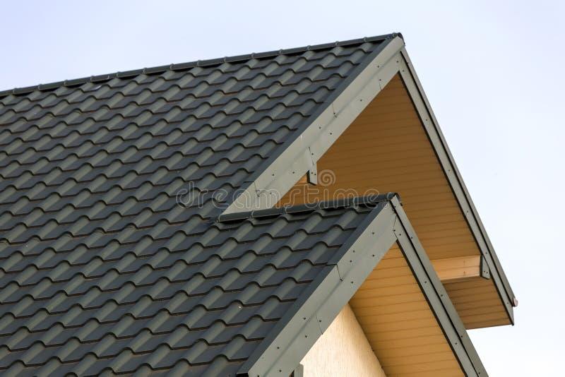Het close-updetail van nieuwe moderne huisbovenkant met shingled groen dak op duidelijke blauwe hemelachtergrond De professioneel stock afbeeldingen