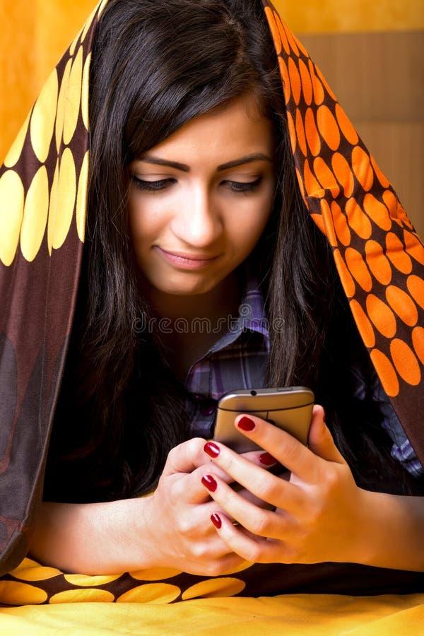 Het close-upportret die van mooie tiener mobil telefoon met behulp van verborg royalty-vrije stock fotografie