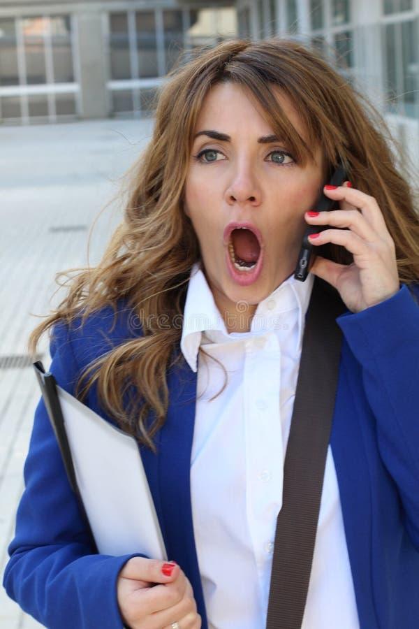 Het close-upportret schokte bedrijfsvrouw, werknemer het spreken op celtelefoon die onplezierig gesprek hebben stock fotografie