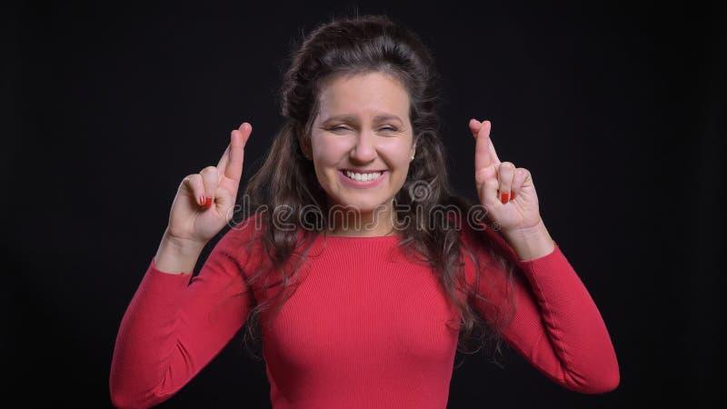 Het close-upportret van aantrekkelijk Kaukasisch wijfje die op middelbare leeftijd haar vingers hebben kruiste in bezorgdheid en  stock afbeelding
