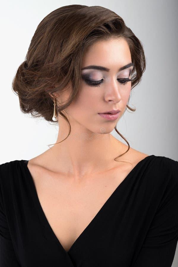 Het close-upportret van brunette met avondmake-up en verzameld haar in een zwarte kleding met ogen sloot status op een lichte bac royalty-vrije stock fotografie