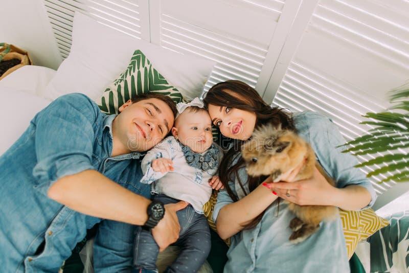 Het close-upportret van de gelukkige familie die met het jonge geitje en het konijn op het bed liggen Boven mening royalty-vrije stock foto