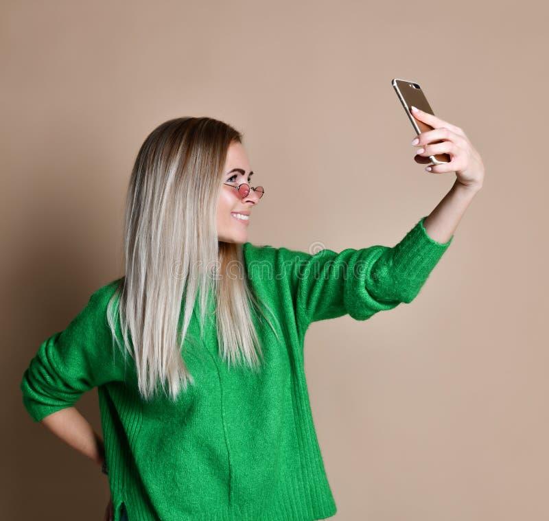 Het close-upportret van de jonge vrolijke vrouw van het manierblonde in sweaterslijtage maakt selfie op smartphone, over beige ac stock foto