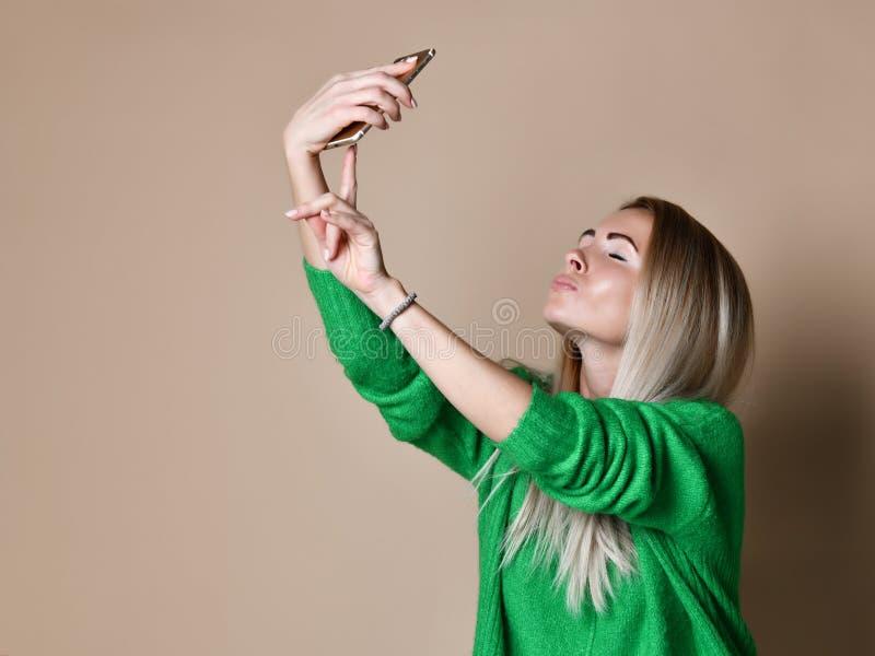 Het close-upportret van de jonge vrolijke vrouw van het manierblonde in sweaterslijtage maakt selfie op smartphone, over beige ac royalty-vrije stock foto