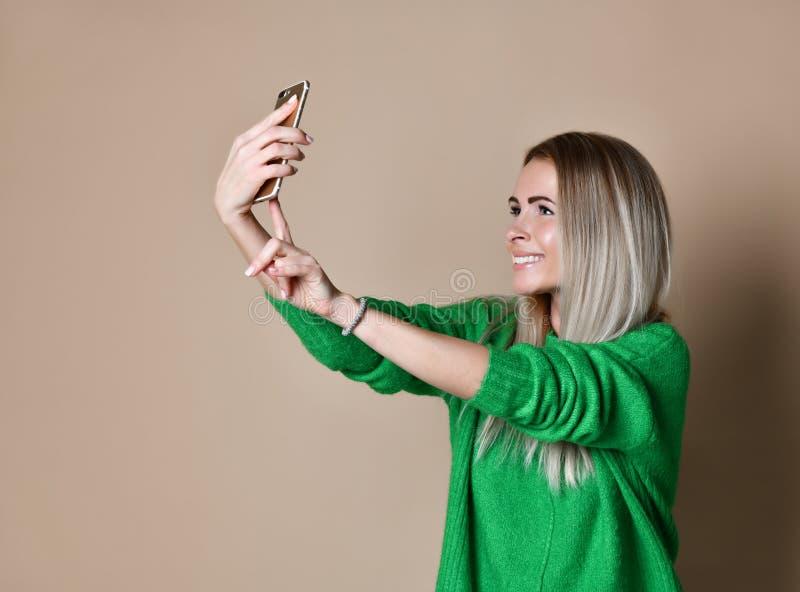 Het close-upportret van de jonge vrolijke vrouw van het manierblonde in sweaterslijtage maakt selfie op smartphone, over beige ac royalty-vrije stock fotografie