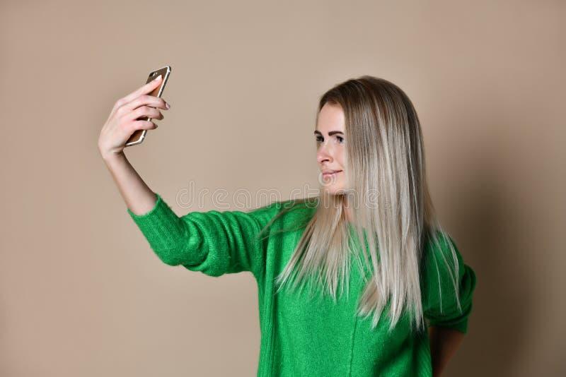 Het close-upportret van de jonge vrolijke vrouw van het manierblonde in sweaterslijtage maakt selfie op smartphone, over beige ac stock afbeeldingen