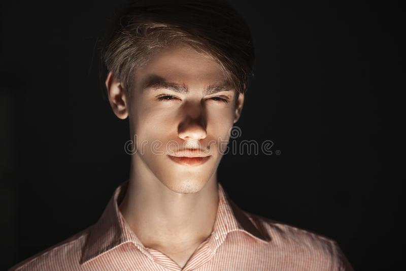 Het close-upportret van de Kaukasische aantrekkelijke jonge mens knipperde zijn ogen het licht glanst van onderaan Ge?soleerde st stock foto's