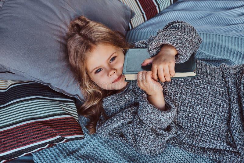Het close-upportret van een klein meisje in warme sweater houdt verhalenboek terwijl het liggen op bed royalty-vrije stock foto