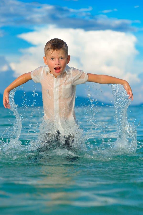 Het close-upportret van een knappe jongen in nat slank geschikt overhemd springt en fladdert over het water, heel wat plonsen en stock afbeeldingen