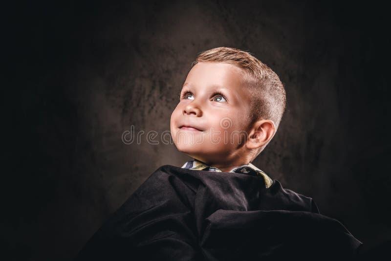 Het close-upportret van een leuke het glimlachen jongenszitting op een stoel met de zwarte salonkaap en wacht op een kapper royalty-vrije stock foto's