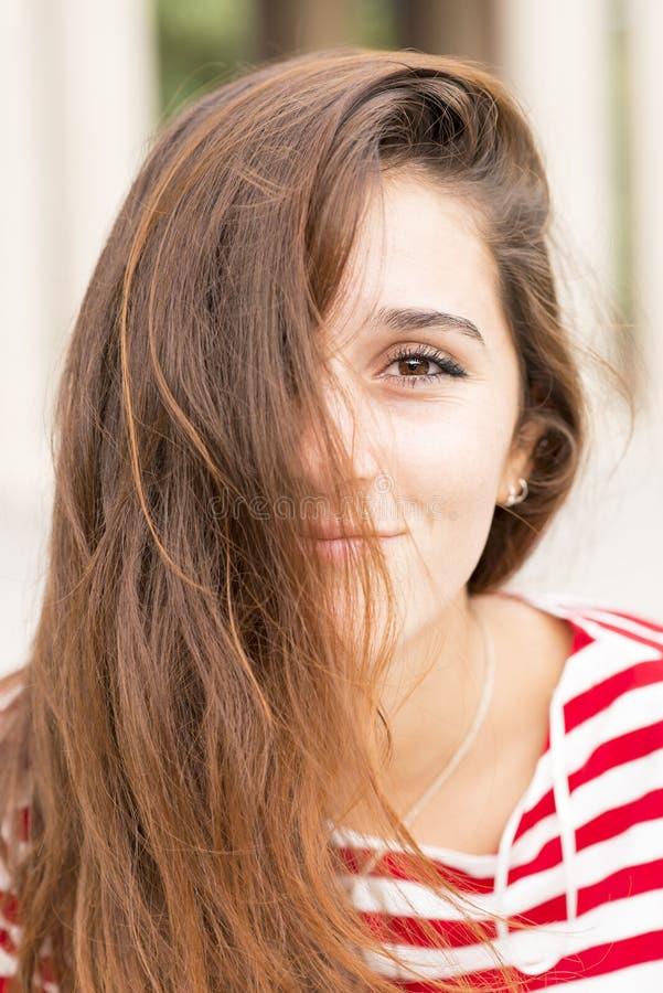 Het close-upportret van gelukkige vrouw behandelt haar gezicht met haar, haren royalty-vrije stock afbeelding