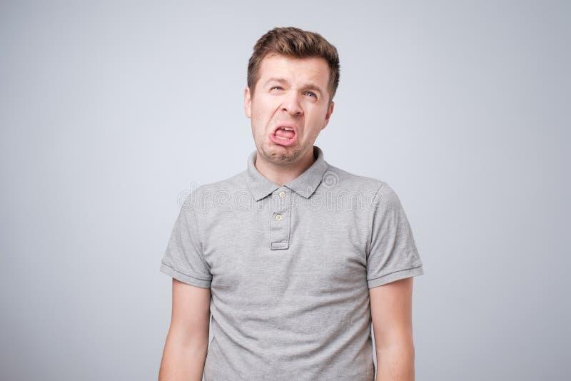 Het close-upportret van grappige boze jongelui intimideert de mens die zijn tong plakken uit bij u cameragebaar stock afbeeldingen