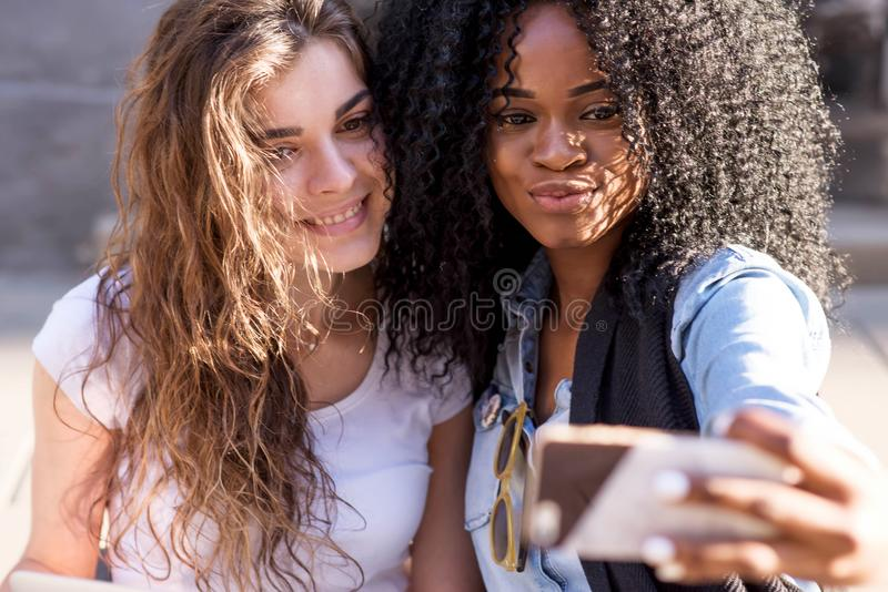 Het close-upportret van jonge aantrekkelijke gemengde race twee girlfrirned het nemen selfie op de mobiele telefoon openlucht stock afbeeldingen