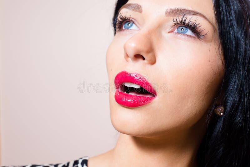 Het close-upportret van mooie verleidende donkerbruine jonge sexy vrouw met blauwe ogen, snakt zwepen, rode lippenstift die omhoo royalty-vrije stock foto