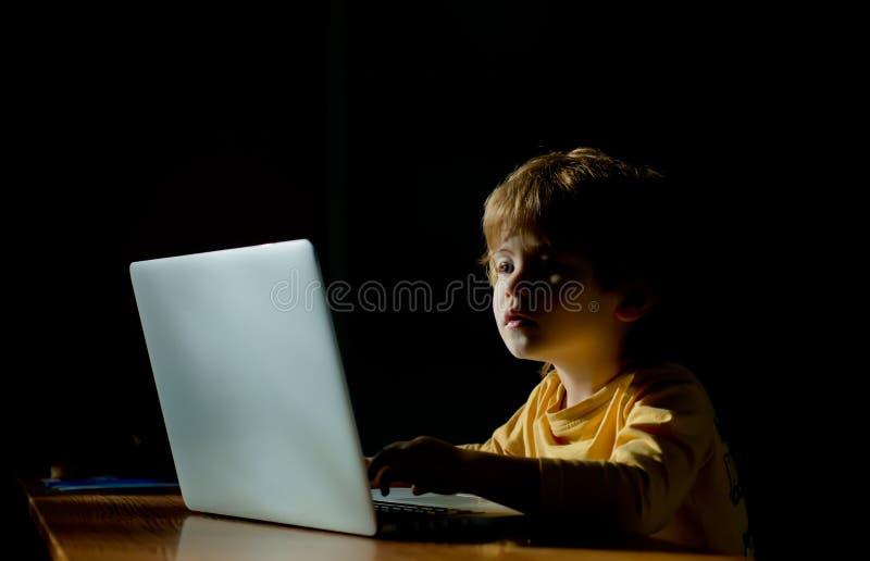 Het close-upportret van Prodigy-de Programmeur van de Jong geitjehakker bij datacentrum vulde met de monitorschermen Kinderen Dig stock fotografie
