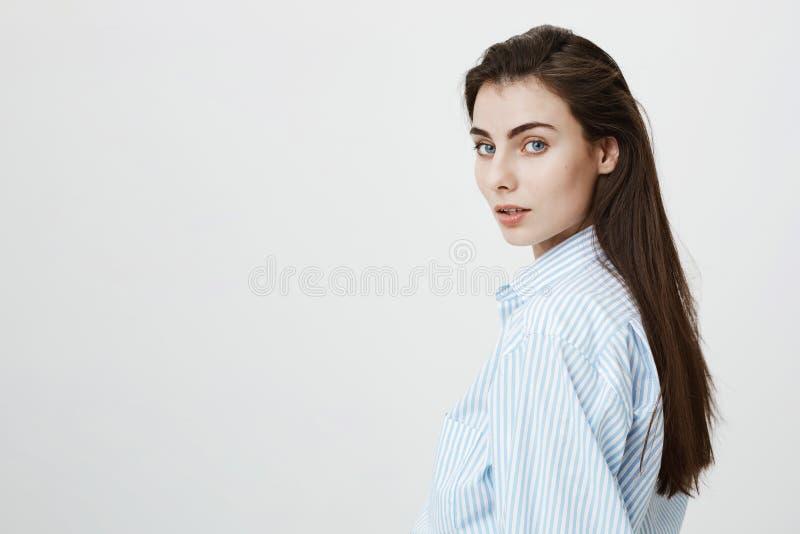 Het close-upportret van sensuele Europese student draaide aan camera terwijl status tegen grijze achtergrond Het meisje liep stock fotografie