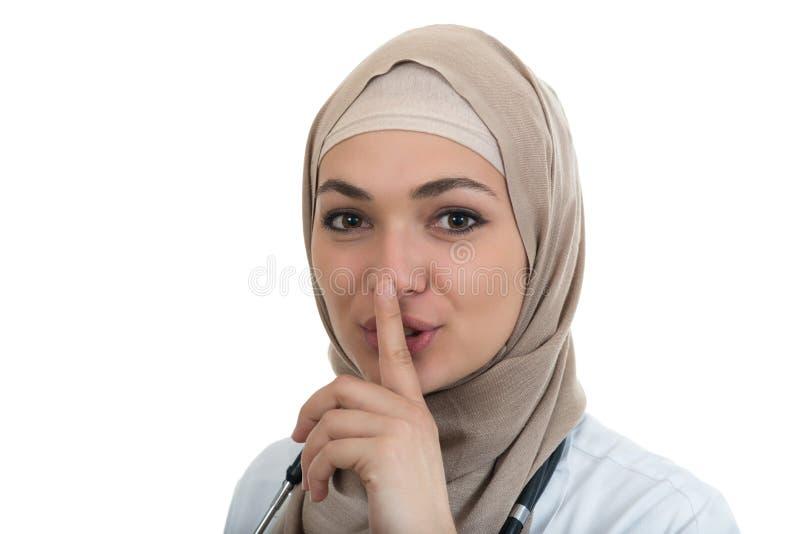 Het close-upportret van vriendschappelijke, zekere moslim met hijab arts het tonen shh zucht, stilte stock afbeelding
