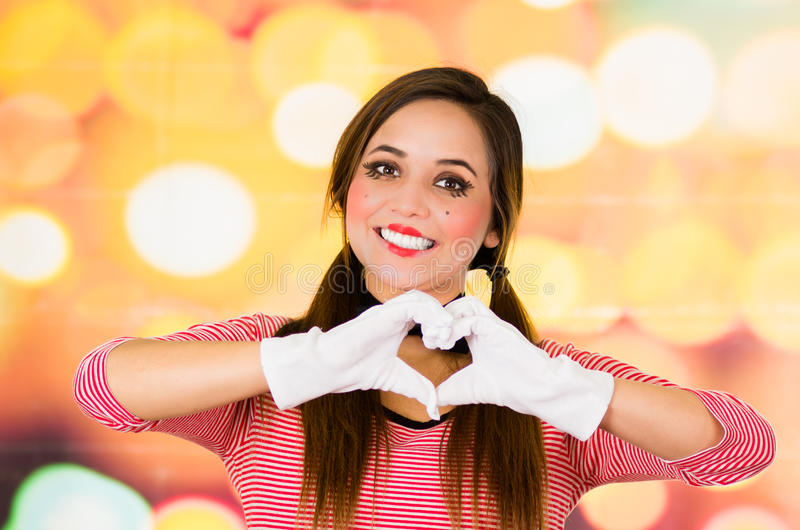 Het close-upportret van vrouwelijke clown bootst het maken van een hart met handen na royalty-vrije stock foto's