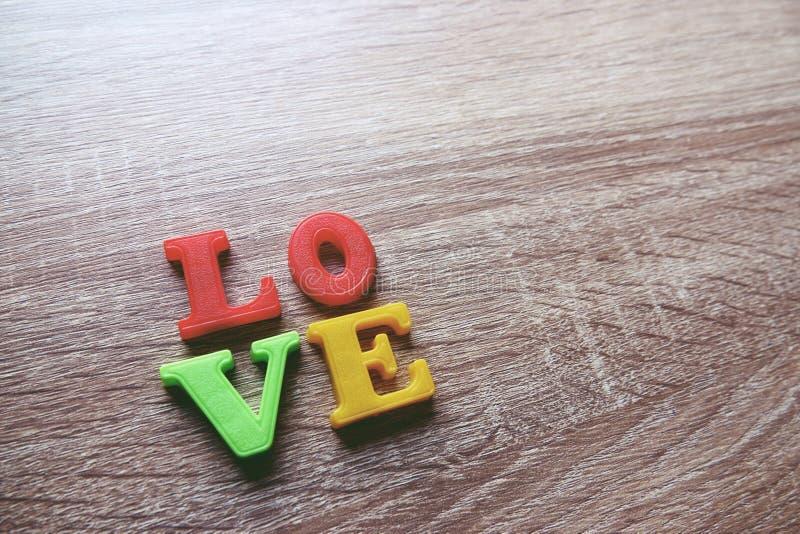 het Close-upschot van het 'liefde 'woord met een selectieve nadruk van de kleurrijke magnetische brieven voor de Dag van Valentin stock afbeeldingen