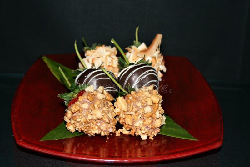 Het close-upschot van Aardbeien in macadamia notenchocolade en kokosnoot worden ondergedompeld schilfert op een rode glasplaat af stock foto