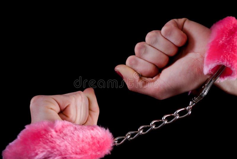 Het close-upwijfje dient handcuffs met roze gezwollen in geïsoleerd op zwarte achtergrond stock afbeelding