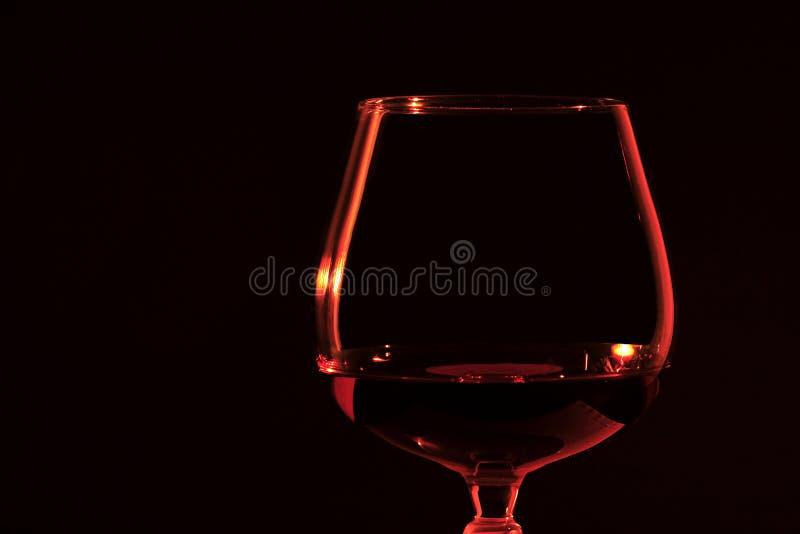 Het Cognacglas van de brandewijn in kaarslicht stock foto