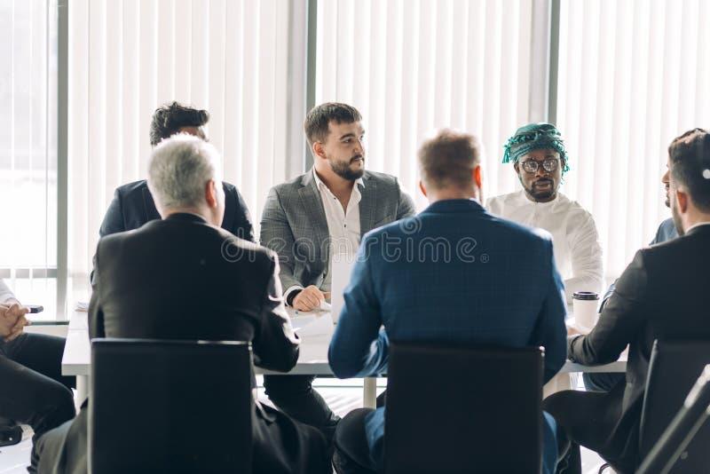 Het collectieve commerciële team tussen verschillende rassen met vrolijke leider in een vergadering, sluit omhoog stock afbeelding