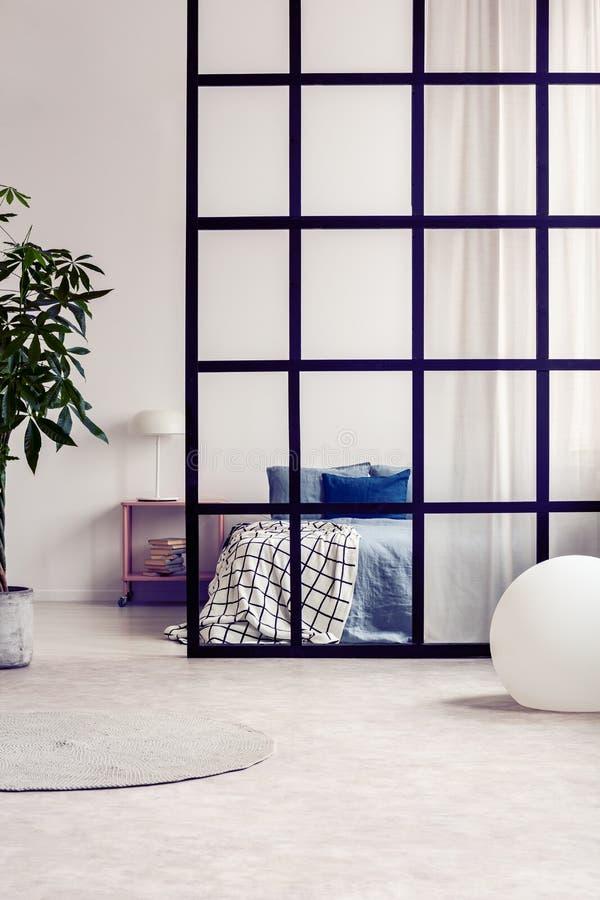 Het comfortabele bed van de koningsgrootte met blauw beddegoed in heldere open planzitslaapkamer met verdeling stock fotografie