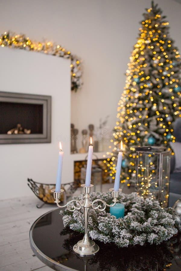 Het comfortabele binnenland van de winterkerstmis met kaarsen, open haard en Kerstboom royalty-vrije stock foto