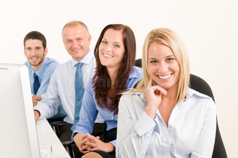 Het commerciële gelukkige team zit in lijn achter lijst stock foto