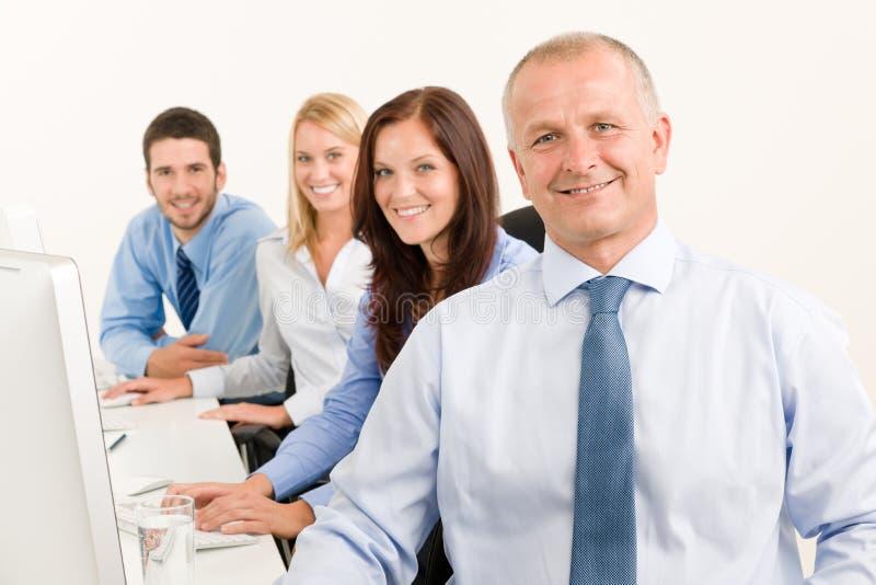 Het commerciële gelukkige team zit in lijn achter lijst stock fotografie
