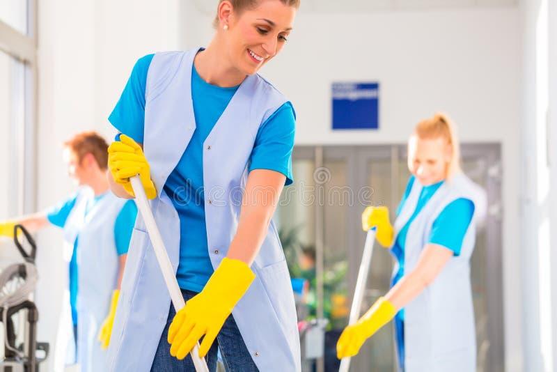 Het commerciële het schoonmaken brigade werken stock fotografie