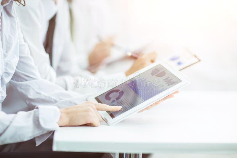 Het commerciële team die digitale tablet gebruiken voert analyse van marketing grafiek uit stock afbeeldingen