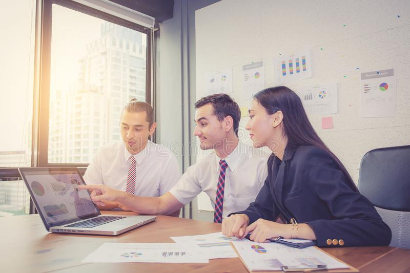 Het commerciële team die een vergadering hebben die laptop met behulp van tijdens een vergadering en stelt voor royalty-vrije stock afbeeldingen