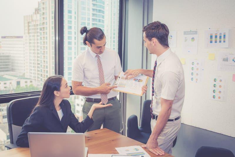 Het commerciële team die een vergadering hebben die laptop met behulp van tijdens een vergadering en stelt winst met grafiek en g stock afbeelding