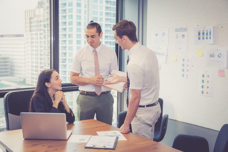 Het commerciële team die een vergadering hebben die laptop met behulp van tijdens een vergadering en stelt winst met grafiek en g royalty-vrije stock fotografie