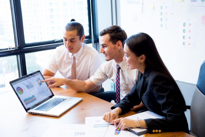 Het commerciële team die een vergadering hebben die laptop met behulp van tijdens een vergadering en stelt winst voor stock foto