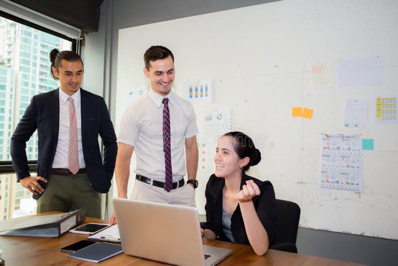 Het commerciële team die het gebruiken van laptop tijdens een vergadering hebben en stelt voor royalty-vrije stock afbeelding