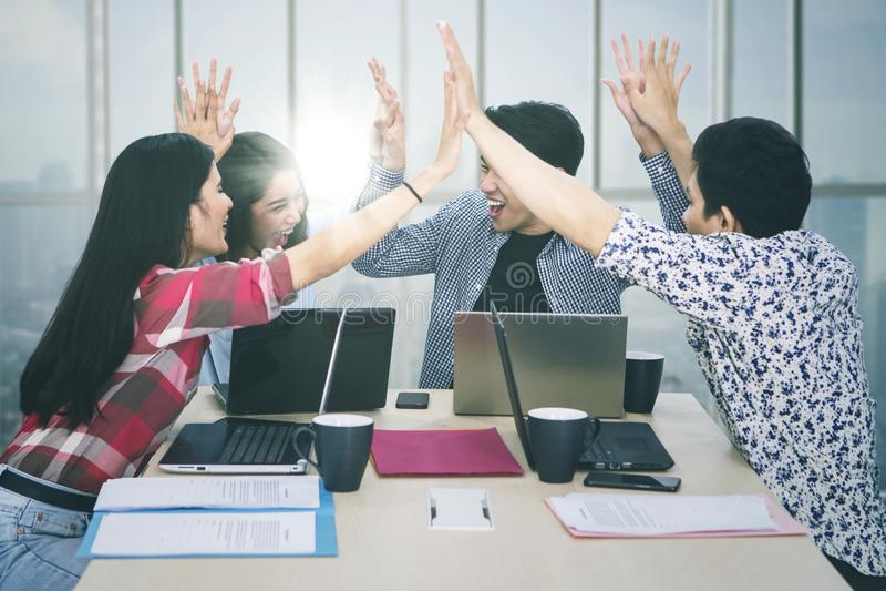 Het commerciële team geeft hoge vijf handen dichtbij het venster stock fotografie